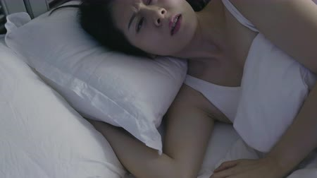 paplan : slow motion of scared asian lady sit up with frowning face hand touching hair forehead. Restless dreams of sleeping woman interrupted by waking up for nightmares from white bed in bedroom at night.
