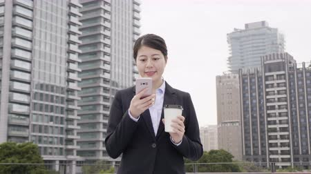 korejština : slow motion successful asian businesswoman wearing suit using modern smartphone and drinking coffee to go before going to work early in morning. young female worker walking to office building.