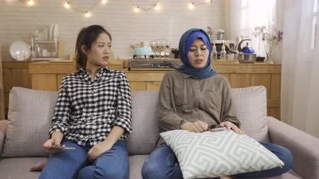korejština : chinese and arabic ethnic female best friends playing game on internet on cellphone losing. young asian girls complaining angry arguing with bad teamwork. upset female on couch with mad emotion talk