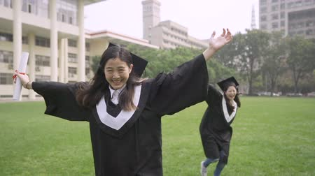 diplom : slow motion Group japanese girl friends having fun running on green meadow summer graduation day. young asian women college students wear gown and cap. female mortarboard fall down on grass campus Dostupné videozáznamy
