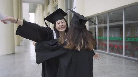 autêntico : slow motion happy college girls students carefree open arms hands hugging with love friendship. graduates asian women with graduation gowns caps standing campus building congratulating. real moments