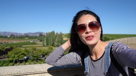 éretlen : asian lady blogger tourist having video phone call showing with hand gesture beautiful nature wineries vineyard in europe. young girl waving hands face camera wear sunglasses smiling attractive talk