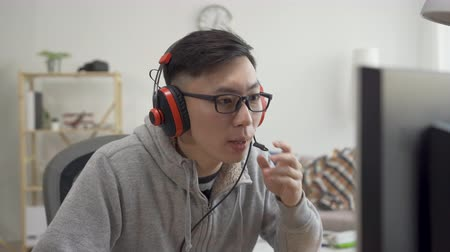 walkthrough : young asian man in headset with computer playing game at home and streaming walkthrough video talk with partner.