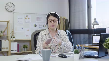 sluch : slow motion young asian casual business woman with laptop and listening music via headphone. Dostupné videozáznamy