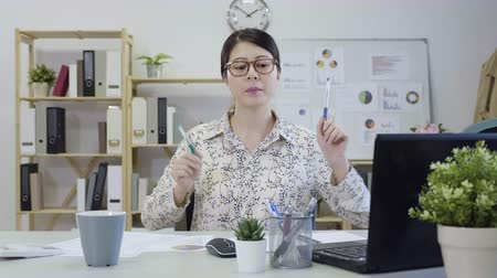 monitor de computador : Happy asian female employee in casual wear listening music and playing with pens as drumming on desk in office.