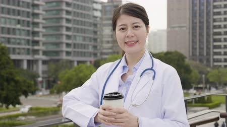 手すり : elegant nurse in lab coat and stethoscope with city skyscraper and park in background. 動画素材