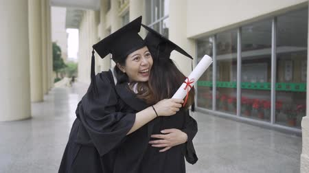 diploma : slow motion asian graduation college students having fun hugging and congratulating each other. friendship love authentic lifestyle. chinese girls in gowns hold diploma out building campus university