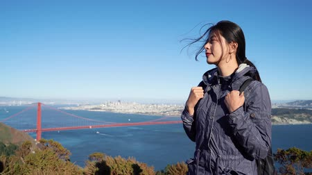 hátizsákkal : Portrait of Chinese woman hiker standing in front of Golden Gate Bridge on mountain top flicks hair resting relax. Asian female tourist with hair blowing in wind visiting San Francisco usa blue sky. Stock mozgókép