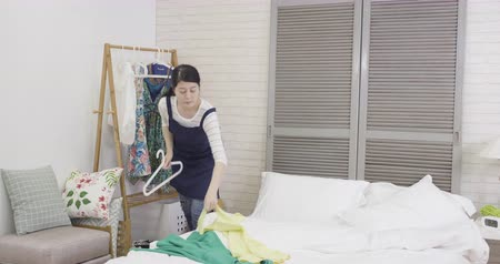traje de passeio : slow motion of chambermaid doing house service housekeeping in bedroom. young asian female housemaid hanging clothes on hanger putting on clothing rack wardrobe in bright modern apartment.