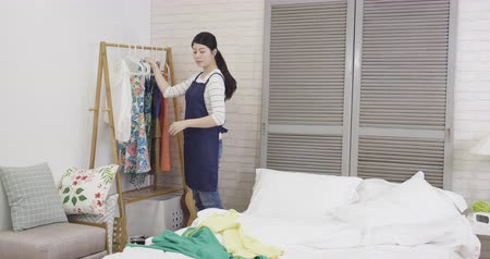 housekeeper : beautiful elegant housewife doing house chores tidy up messy bed in bedroom with full of clothes. young asian girl maid putting colorful dresses on hanger hanging on clothing rack wardrobe at home.