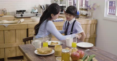 arrumado : slow motion asian mother sitting at kitchen wooden table getting kid dressed for elementary school at home. chinese mother fixing tired little girl uniform dress and tell her go to seat eat breakfast