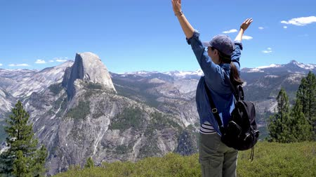 braços levantados : back view of happy woman hiker with backpack enjoying nature on grass meadow on top of mountain cliff with sunshine outdoor. Freedom concept. half dome trail view yosemite national park california