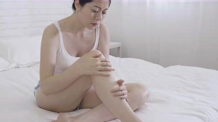 gondos : slow motion unhappy asian female in shorts and tank top sitting on bed hands massage touching legs. young girl feeling bad dry skin frowning looking at feet. woman lazy dislike health skin care. Stock mozgókép