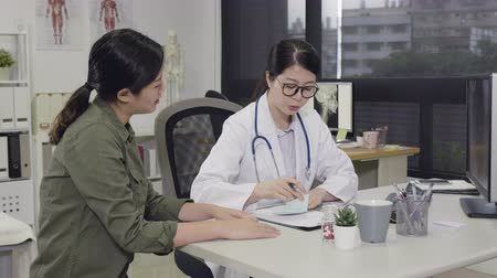 коллега : slow motion of young asian female doctor working in office hospital. girl medical staff worker writing on memo giving prescription to woman patient and explaing about medicine. profession health care