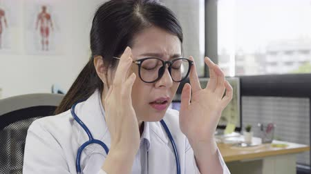 wzrok : slow motion overworked at work painful doctor woman at desk massages tired eyes. frowning exhausted nurse eye hurt in glasses in hospital clinic office hard working. eyesight problems concept.