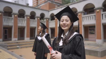 derece : Happy group of mature students on graduation day. slow motion elegant asian woman smiles to camera carefree raise hands with diploma and excited face. chinese best friend standing in background.