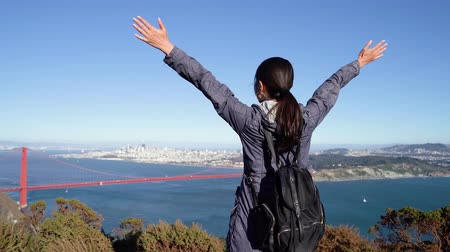 hátizsákkal : back rear view of asian girl backpacker carefree arms wide open golden gate bridge in san francisco usa enjoying vacations in the capital city discovering new nature mountain place enjoy blue sky sea Stock mozgókép