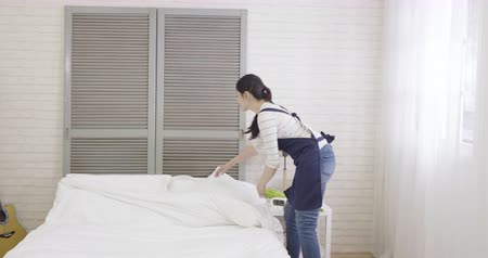 yorgan : beautiful asian female household doing house chores in cozy apartment. young housewife mom cleaning up bedroom making up bed with white sheet quilt walking around in room at home. elegant maid work Stok Video