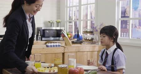 asya mutfağı : asian mother and child having breakfast in kitchen together. elegant businesswoman in suit taking out fruit on plate eating with daughter in school uniform in morning. woman power single mom lady. Stok Video