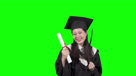 выражающий : Young asian japanese woman wearing graduate uniform over isolated green background celebrating surprised and amazed for success with arms raised showing diploma. cheerful college girl excited emotion