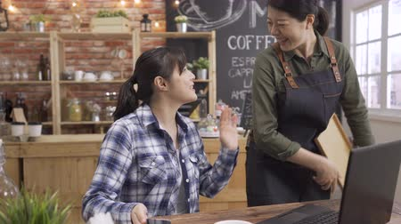 patron : two young asian woman in cafe using sharing smart phone and having funny conversation. waitress giving order coffee walk close to customer good friend. girls friendship cheerful chatting service.