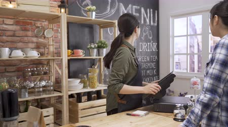 ресторан : asian female customer ordering at counter in coffee shop. friendly woman waitress finger touching 3d rendering point of sale system for store management. two ladies looking at menu in cafe service Стоковые видеозаписи