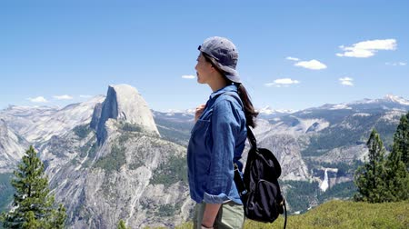 kap : Young smiling chinese woman hiker manage to gets to top standing in front of beautiful dolomites and blue sky landscape in yosemite surroundings. female backpacker enjoy half dome trail view outdoor Stock mozgókép