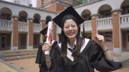 dişlek : Slow motion attractive Asian girl graduating student in gown and mortar board standing on campus smiling raise hands with diploma looking at camera. Youth education concept. best friend in background
