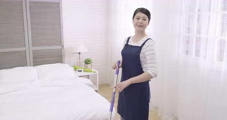 arrumado : slow motion young asian elegant woman housewife cleaning wooden floor with mop in cozy bedroom. proud professional housemaid doing room service tidy up apartment looking at camera smiling attractive