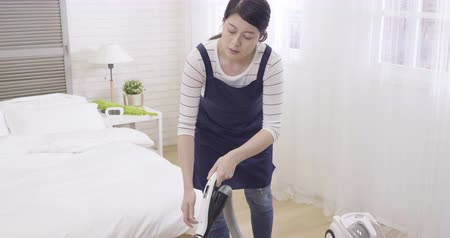disinterest : slow motion of disinterest asian woman cleaning bedroom vacuum cleaner. young chinese household in apron tired with hurting back painful. housewife having health problem backache doing house chores Stock Footage
