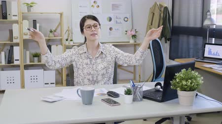 direkt : slow motion young small business office lady immersed in music gesturing with hands as conducts to melody beat. female employee sitting at desk in workplace daydreaming about her dream career job
