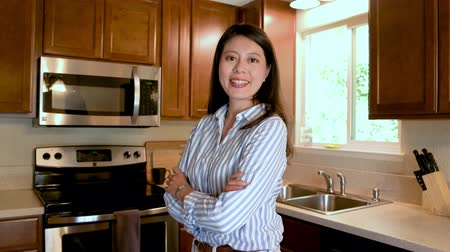 dienstbode : elegant young asian woman employee businesswoman stand at home kitchen in wooden country style house in america. morning beautiful office lady before work face camera smiling in smart casual wear.