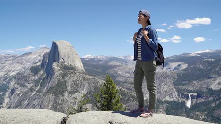 sandali : full length young happy asian woman with backpack standing on rock looking face sunshine sightseeing view in half dome trail yosemite. beautiful female tourist hiker in sandals climbing outdoors. Filmati Stock