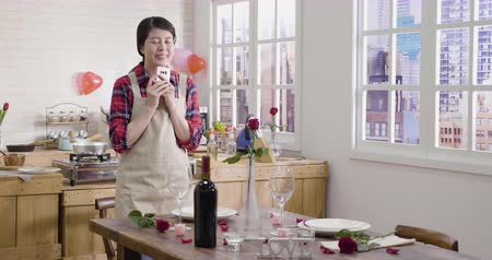 vaas : slow motion of attractive asian woman standing next to romantic valentine table texting on mobile phone. Smiling laughing female in love prepared ready for beautiful decorated dinner desk with roses.