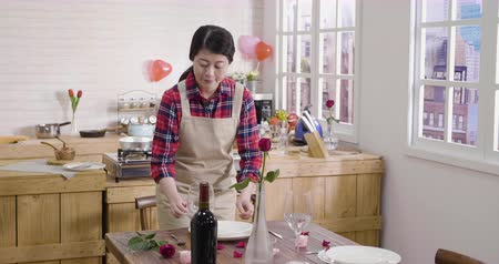 домохозяйка : asian woman prepare on valentines day in modern cozy apartment. elegant girl doing table setting for romantic dinner concept. young lady moving place of dish knife fork and glass on flower desk.