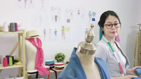samples of fabric : elegant young asian chinese woman fashion designer looking at cloth samples on mannequin in workshop. girl professional worker examining scarf color with needle taking from shelf in modern studio. Stock Footage