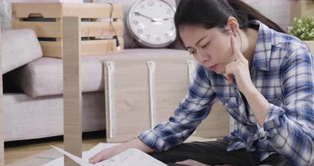 хмурый : young puzzled asian woman reading assembly instructions of wood furniture in living room at move new home. beautiful frowning lady sitting on floor in apartment relocation. DIY lifestyle concept.