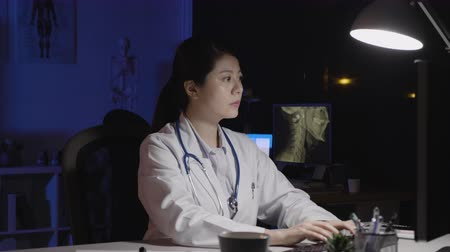 marad : woman doctor typing medical receipt to patient. asian female physician working at computer in clinic office at night. overworked young lady with stethoscope in dark hospital. Stock mozgókép
