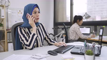 muslim leader : multi fashion designer group teamwork in modern office studio. young muslim boss talking on cellphone checking order with customer changing correcting mistake. chinese woman colleague listen writing