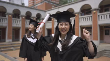 graduação : slow motion smiling female student in academic gown posing positively standing outdoor with best friend. young asian woman wearing cap and gown is holding diploma raising arms having fun university