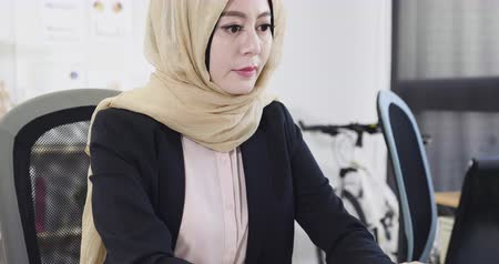 сотрудники : down to up angle close up view of confident arabic superior businesswoman doing work at modern office  in city. islam female ceo in workplace typing on laptop pc replying email to customer in morning