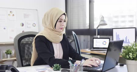 khaki : serious malay businesswoman in yellow khaki headscarf typing on laptop computer at working desk in office. young professional female arabic manager working on notebook pc in modern workplace. Stock Footage
