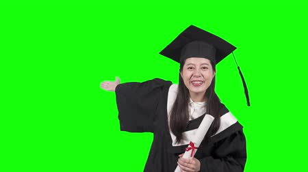 Happy asian female graduate student holding diploma isolated on green background. college girl in gown and cap waving hands say hi and showing side excited. young chinese woman in academic dress. Dostupné videozáznamy