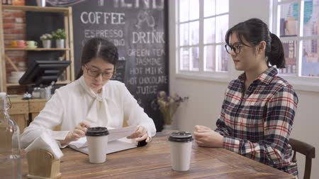 serious asian woman employee sitting at wooden table in coffee shop and interviewing job candidate. confident business lady received resume reading asking question to applicant in cafe bar writing