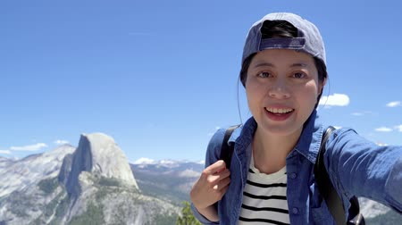 happy girl hiking in half dome trail yosemite and standing on mountain.