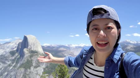 cheerful woman traveler in yosemite showing half dome trail view with hand gesture.