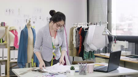 fashion business : Successful tailor entrepreneur woman using laptop checking with sketches paper draws.