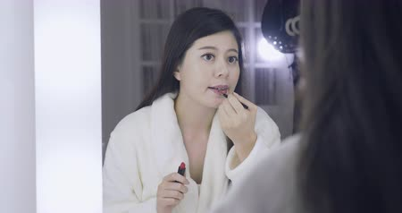 evsahibi : slow movement amazing asian woman doing her makeup in front of mirror.