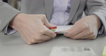 slow motion of asian female hands stapling papers with stapler sitting at desk wearing suit.