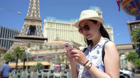 young travel woman in Paris using cell phone in front of Eiffel Tower.